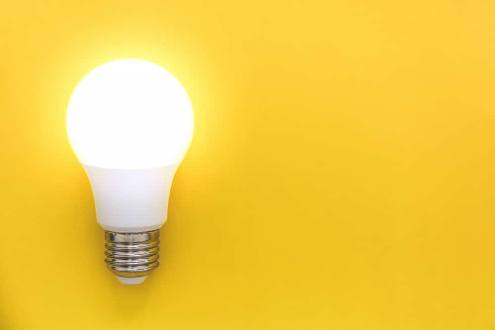 led light bulb on yellow background concept of ideas creativity innovation or saving energy copy space top view flat lay